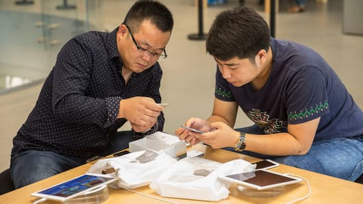 Customers use Apple Inc.'s iPhone 6s at the company's store during the sales launch of the iPhone 6s and iPhone 6s Plus at the IAPM shopping mall in Shanghai, China