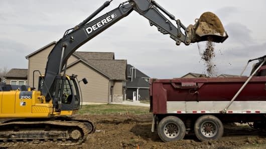 A John Deere 210G excavator loads soil onto a dump truck as a foundation is dug for a new home in Dunlap, Illinois.