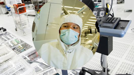 A technician inspects a silicon wafer at the Applied Materials Maydan Technology Center in Santa Clara, California.
