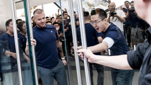 Employees open the doors to Apple's new Canton Road store in the Tsim Sha Tsui district of Hong Kong.