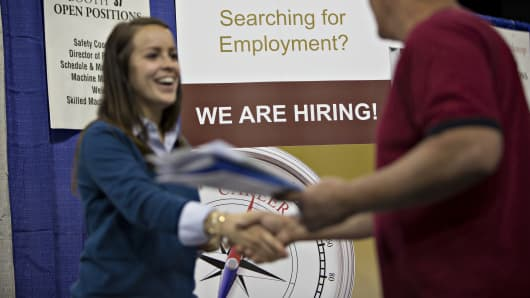A job seeker, right, shakes the hand of a recruiter during the Quad Cities career fair in Moline, Illinois.