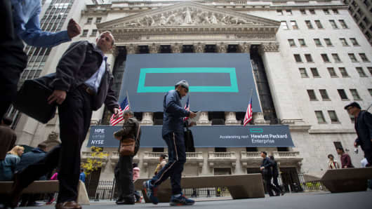 Pedestrians walk past Hewlett Packard Enterprise signage displayed outside of the New York Stock Exchange.