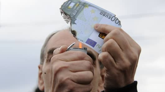 A protester burns a fake one hundred Euro banknote during a demonstration against a new package of tax hikes and reforms in Athens, Greece.