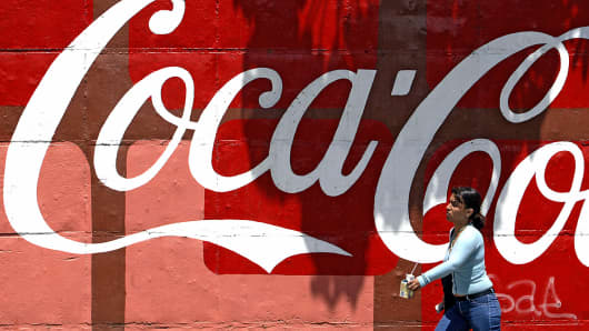 A woman walks past a Coca-Cola advertisement in Caracas, Venezuela.