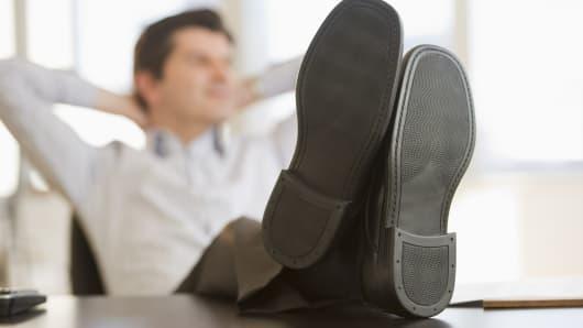 Businessman comfortable, feet up at work