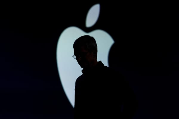 The silhouette of Tim Cook, chief executive officer of Apple Inc., is seen as he exits the stage during the Apple World Wide Developers Conference (WWDC) in San Francisco.