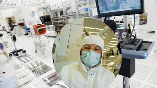 A technician inspects a 300mm silicon wafer at the Applied Materials Maydan Technology Center in Santa Clara, California.