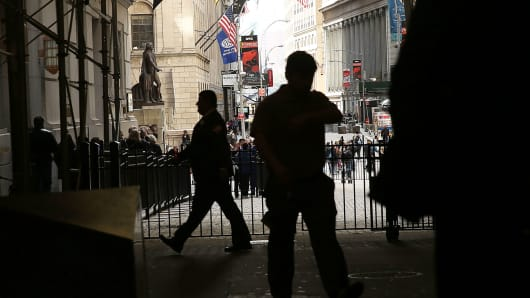 People walk outside of the New York Stock Exchange.
