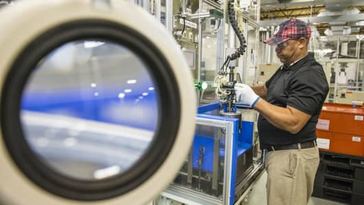 An employee builds a component for hybrid electric vehicle motors at the Toshiba International Corp. manufacturing facility in Houston.