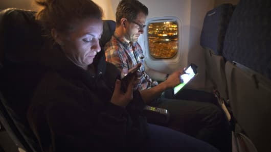 People use their smart devices on an American Airlines airplane, which is equipped with Gogo Inflight Internet service, enroute from Miami to New York.