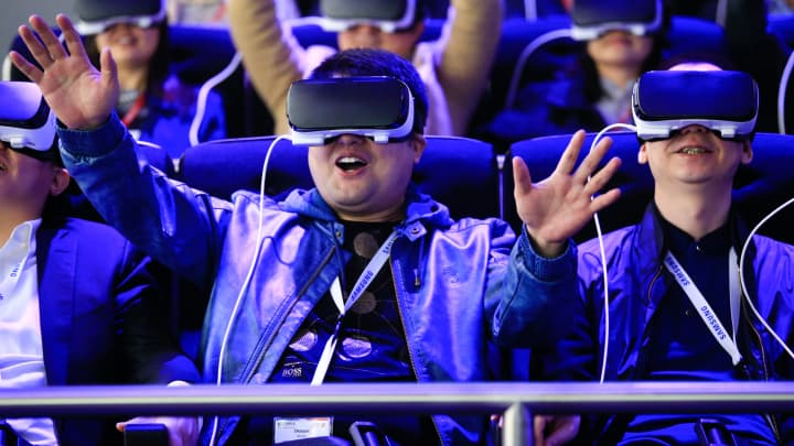 Delegates try a roller coaster ride using Gear VR (virtual reality) headsets, manufactured by Samsung Electronics Co., at the Mobile World Congress in Barcelona, Spain, on Monday, Feb. 22, 2016.