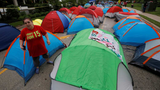 A protester walks among tents set up outside the McDonald's headquarters during a demonstration calling for higher wages and improved working conditions in the Chicago suburb of Oak Brook, Illinois, U.S., May 25, 2016.