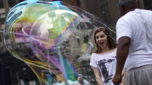 Man in park popping bubble, pop bubbles