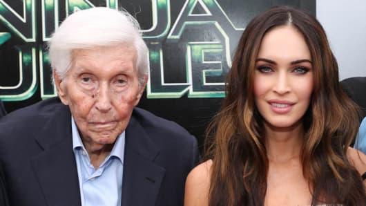 "Redstone poses with Megan Fox at the 2014 LA premiere of ""Teenage Mutant Ninja Turtles."""