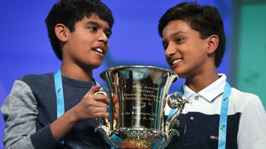 Spellers Nihar Saireddy Janga (L) of Austin, Texas and Jairam Jagadeesh Hathwar (R) of Painted Post, New York hold a trophy after the finals of the 2016 Scripps National Spelling Bee May 26, 2016 in National Harbor, Maryland.
