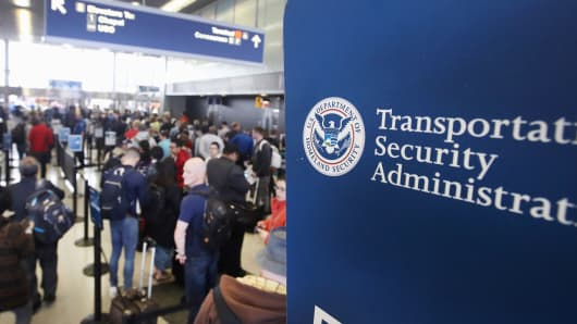 Passengers at O'Hare International Airport wait in line to be screened at a Transportation Security Administration (TSA) checkpoint in Chicago.