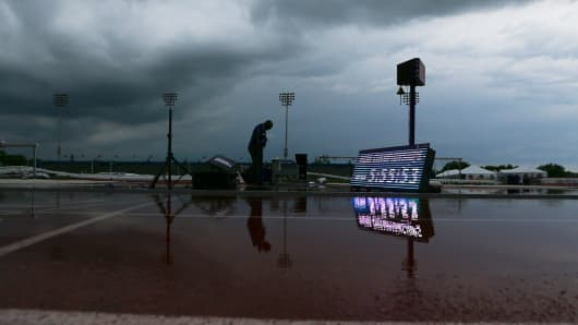 A meet official surveys the damage to the field after severe weather and high winds interrupted the NCAA West Region track and field meet on Thursday, May 26, 2016, at Rock Chalk Park in Lawrence, Kan.