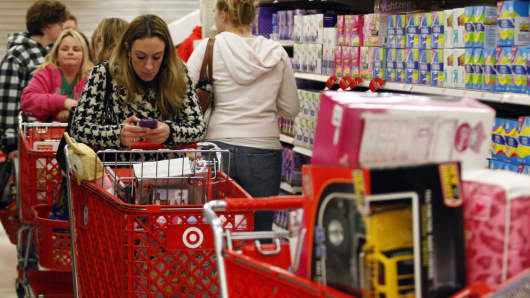 A woman uses her smartphone as she waits in line to checkout at a Target store