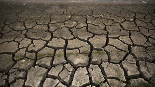 Cracked earth sits next to a pool of water at the dried up Mae Jok Luang reservoir in Chiang Mai, Thailand, on April 23, 2016. An El Nino-induced drought across Thailand is parching crops, leading market forecasters to reduce their production estimates.