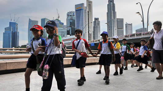 School children walk in line past the financial district during an outdoor excursion at the Marina Bay in Singapore on May 24, 2010.