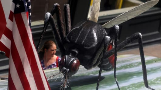 A woman walks past a giant fake mosquito placed on top of a bus shelter as part of an awareness campaign about the Zika virus in Chicago.