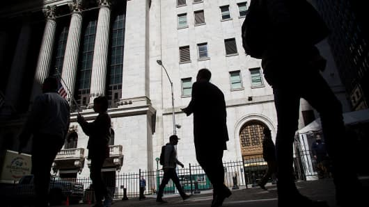 The silhouettes of pedestrian are seen walking past the New York Stock Exchange