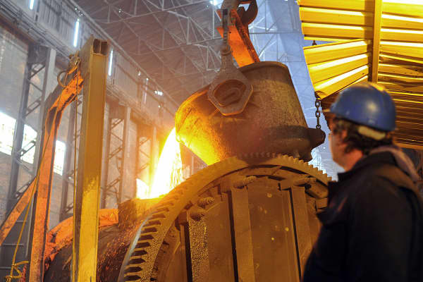 A worker supervises as molten liquid copper is poured into molds.