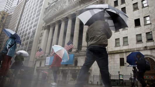 Pedestrians carry umbrellas while walking past the New York Stock Exchange.