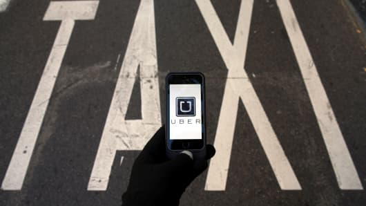 The logo of car-sharing service app Uber on a smartphone over a reserved lane for taxis in a street is seen in this photo illustration taken in Madrid.