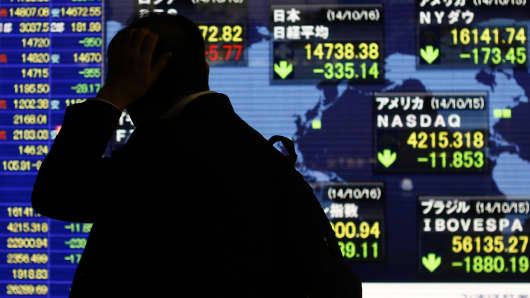 A pedestrian scratching his head looks at an electronic board showing the stock market indices of various countries.