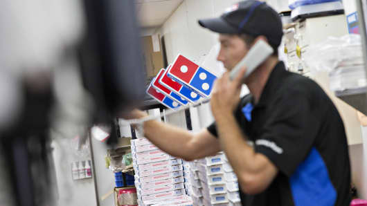 An employee takes a customer's order on the phone at a Domino's Pizza restaurant.