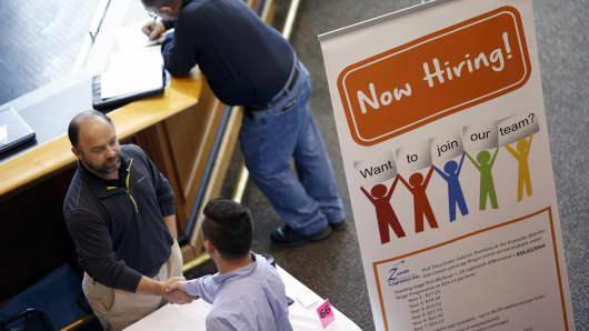 A representative, left, shakes hands with a job seeker during a Job News USA career fair