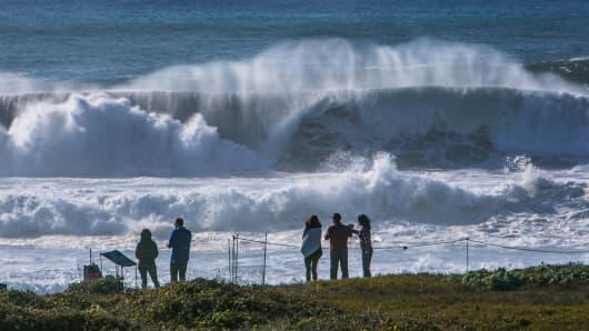 Heavy surf crashes along the coastal rocks and shoreline near the Piedras Blancas Lighthouse, California.