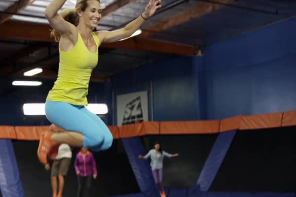 Woman jumps on trampoline at Sky Zone.
