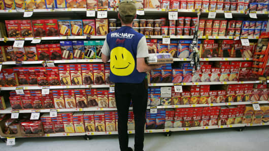 An employee restocks a shelf in the grocery section of a Wal-Mart Supercenter