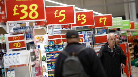 Promotional signs display the price of merchandise as shoppers browse goods inside an Asda supermarket, operated by Wal-Mart Stores in London.
