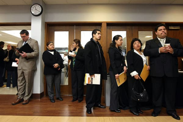 Job seekers wait in line in to fill out a job application