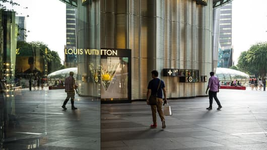 A shopper walks past a Louis Vuitton store, operated by LVMH Moet Hennessy Louis Vuitton SA, in the Ion Orchard mall, jointly owned by CapitaLand Ltd. and Sun Hung Kai Properties Ltd., on Orchard Road in Singapore on Wednesday, March 25, 2015.