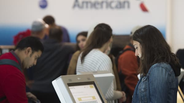 Passengers check in for their flights on American Airlines at Reagan National Airport in Arlington, Virginia