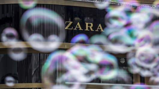 Giant bubbles created by a street artist float past a Zara fashion store.
