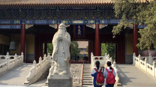 Li Cong, right, and her classmate An Meng walk past a statue of Confucius at the Confucius Temple in central Beijing on June 4, 2016.