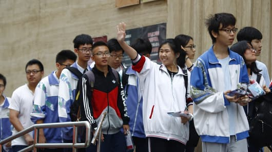 A student waves to her family as she prepares to enter a Beijing exam center to take part in the Gaokao on June 7, 2016.