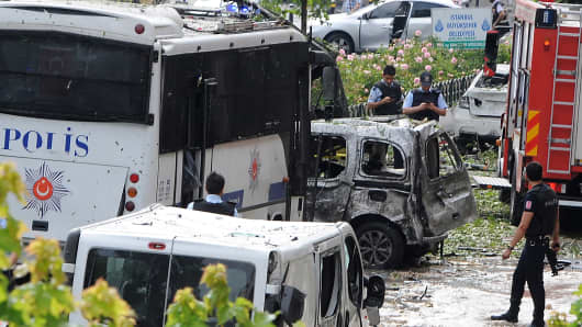 Police officers and rescuers inspect the site of a bomb attack that targeted a police bus in the Vezneciler district of Istanbul on June 7, 2016