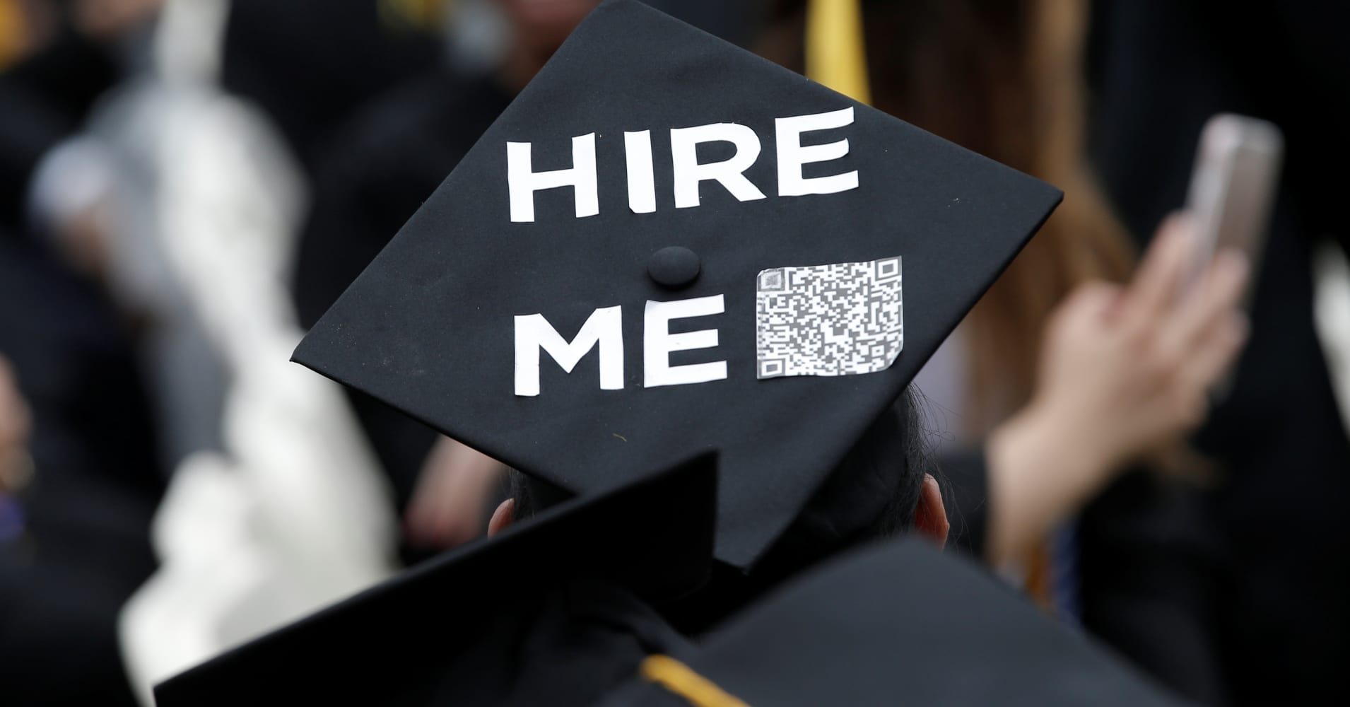 A graduating student of the city college of new york wears a message on his cap