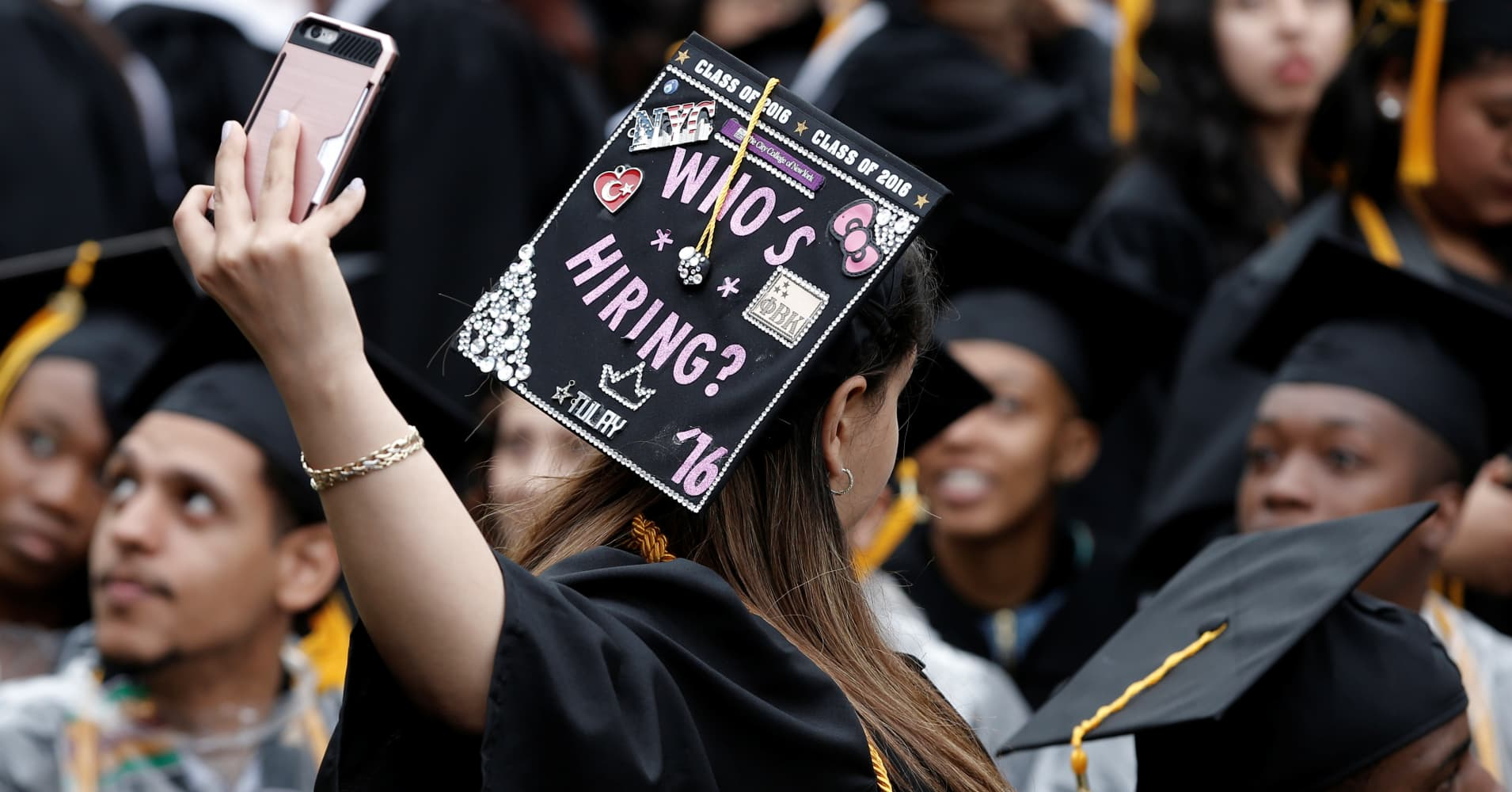 A City College of New York graduate takes a selfie during the commencement ceremony.