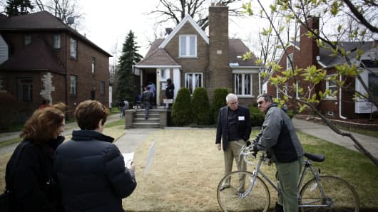 People stand outside of a home for sale in the East English Village neighborhood of Detroit.
