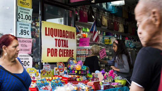 Pedestrians walk past a store that is under liquidation in the Rio Piedras neighborhood in San Juan, Puerto Rico.