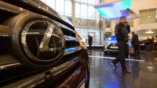 A customer speaks on a mobile phone while passing a Lexus RX270 vehicle for sale inside a Lexus automobile dealership.