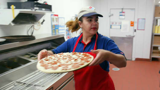 A Domino's employee preparing a pizza.