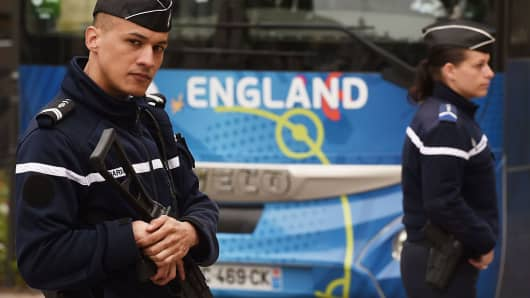 Armed police officers stand by the England team's coach as the players leave their hotel in Chantilly, on June 9, 2016 ahead of Euro 2016.